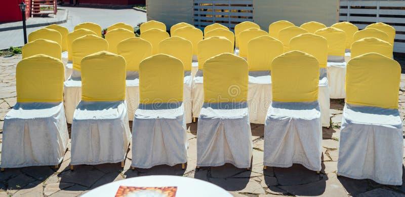 Stolar f?r g?ster p? br?llopceremoni med den utomhus- vit- och gulingsat?ngtorkduken royaltyfri bild