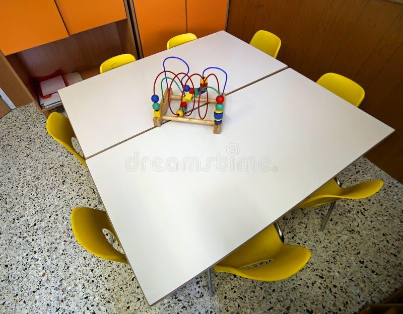 Stolar med en leksak över skrivbordet inom dagiset arkivfoto