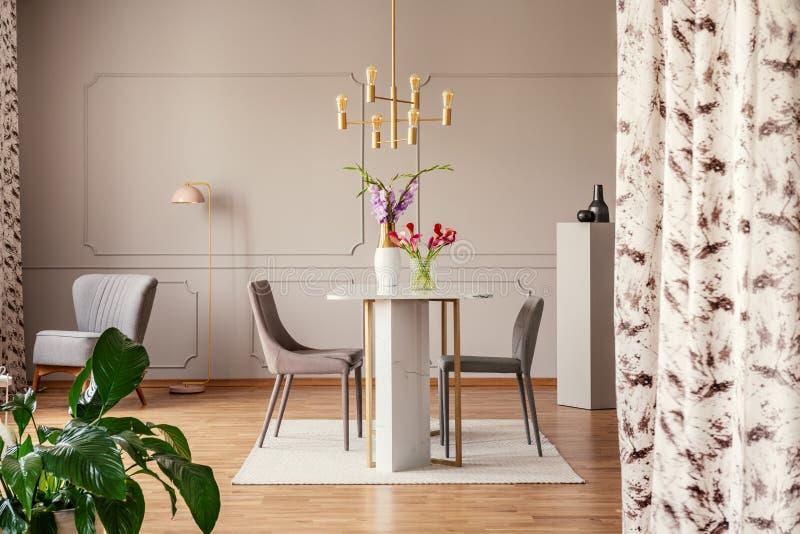Stolar och tabell för guld- lampa ovannämnda med blommor i elegant matsalinre med växten Verkligt foto arkivbilder