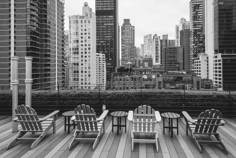 Stolar på ett tak och en sikt av sköldpaddafjärden, i midtownen Manhattan, New York City arkivbilder