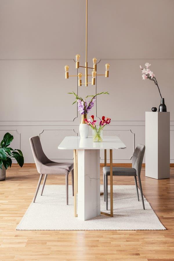 Stolar på tabellen med blommor i modern matsalinre med den guld- lampan och matta Verkligt foto royaltyfri foto