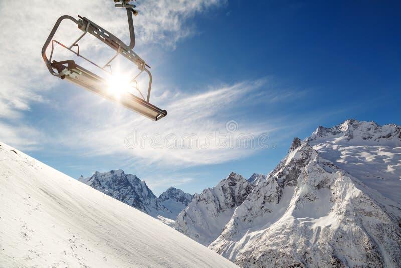 Stolelevator på en bergssida på bakgrund av blå himmel, snö-korkade berg och en ljus vintersol royaltyfri bild