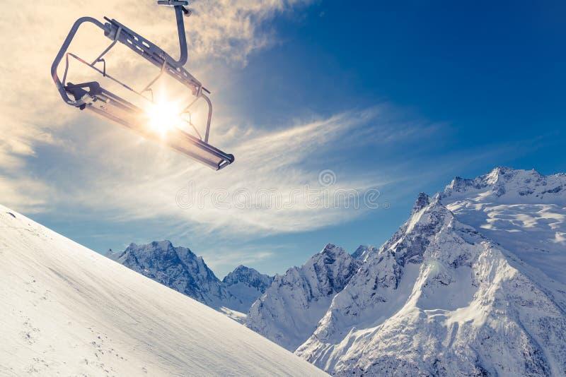 Stolelevator på en bergssida på bakgrund av blå himmel, snö-korkade berg och en ljus vintersol arkivbilder