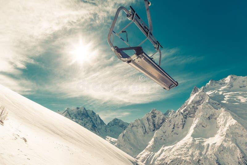 Stolelevator på en bergssida på bakgrund av blå himmel, snö-korkade berg och en ljus vintersol arkivbild