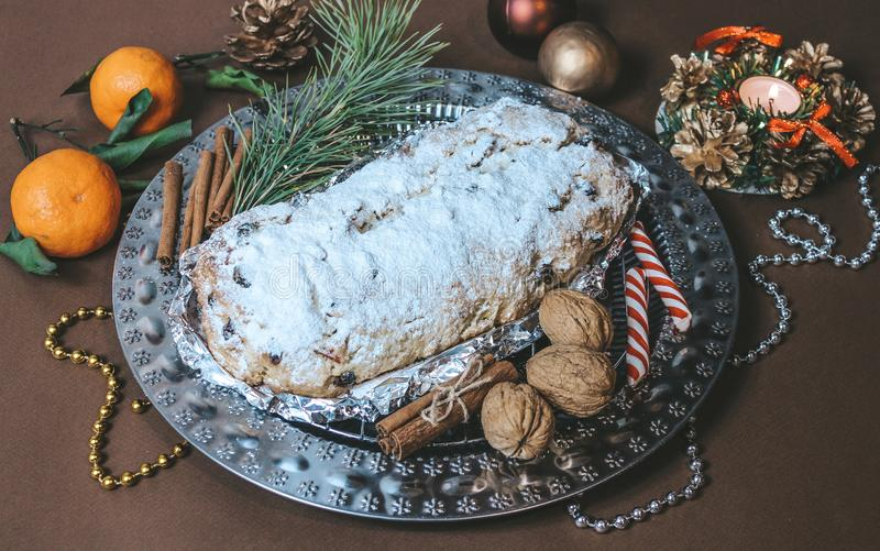 Stollen Christmas Cake on a brown background with glittering decorations stock photos