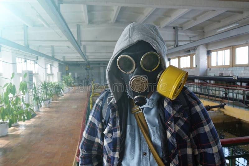 Stolpe-apokalyptiskt Grabben i gasmasken står i en övergiven byggnad arkivfoto