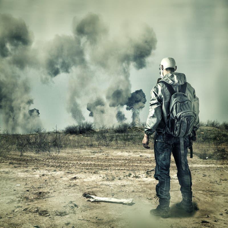 Stolpeapokalyps. Man i gasmasken, explosioner arkivbild