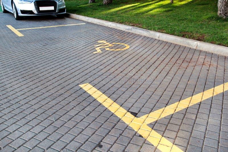 Stolpen med rörelsehindrad parkeringsplats och tecknet framme av parkeringsfjärden i parkeringshus/markerade parkering för folk m arkivbild