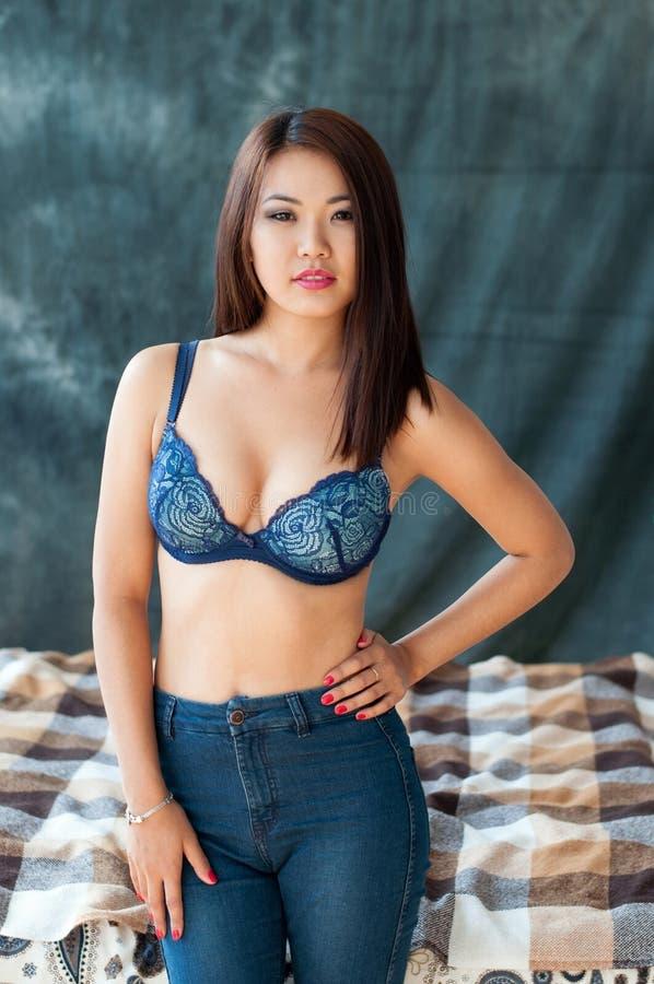 Stolt asiatisk kvinnlig i behå och jeans som står nära säng arkivfoto