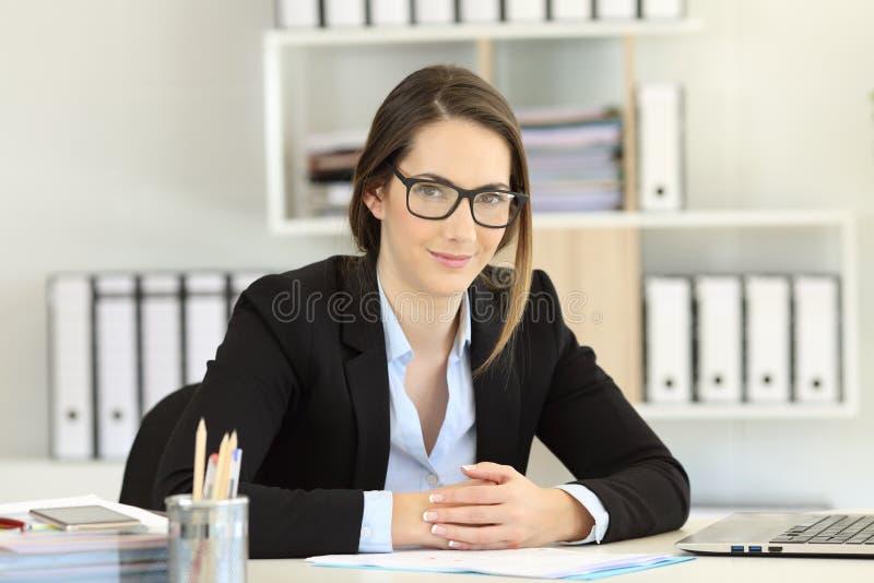 Stolt bärande glasögon för kontorsarbetare som ser kameran fotografering för bildbyråer