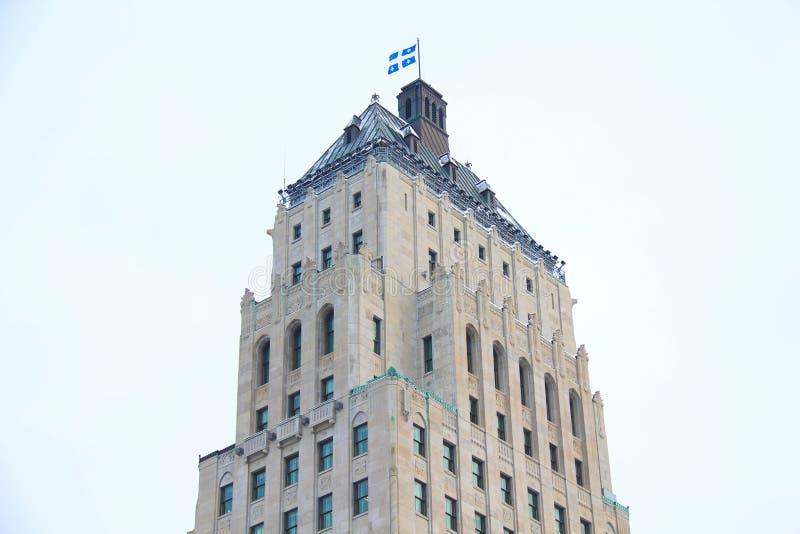 Stolt blå och vit flagga av det Quebec landskapet som överst står av en byggnad arkivbilder