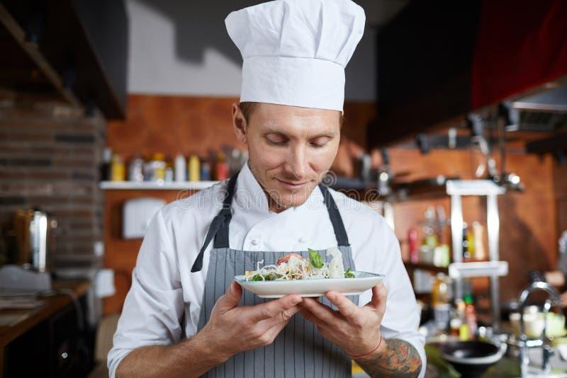 Stolt kock Presenting Dish arkivbild