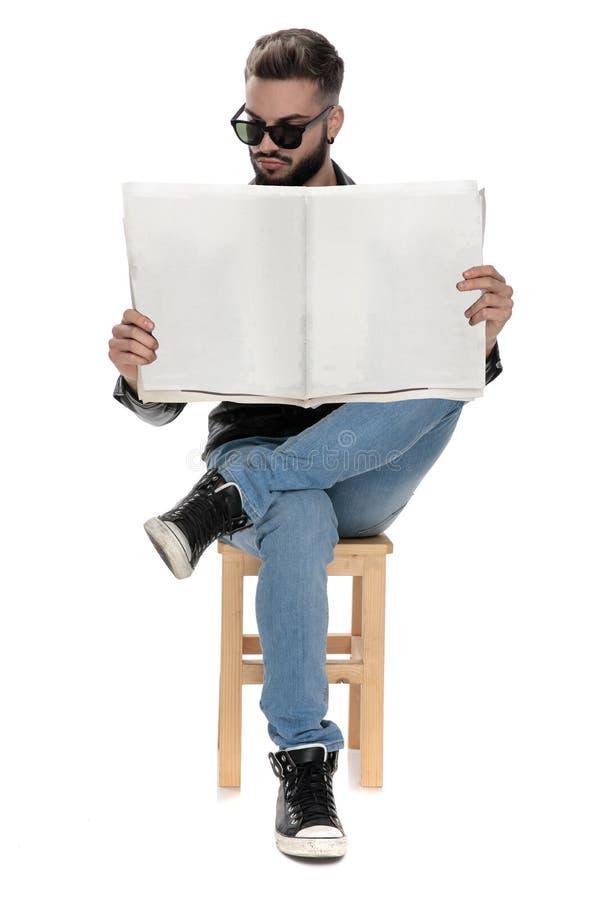 Stolt man med solglasögon som läser tidningen royaltyfria foton
