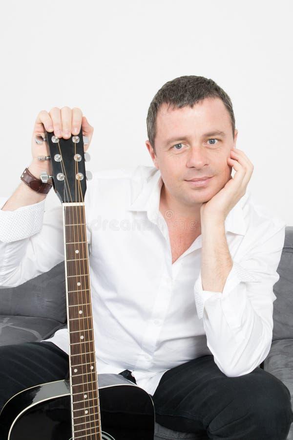 Stolt man som hemma poserar med gitarren i livingroomsoffa royaltyfri bild