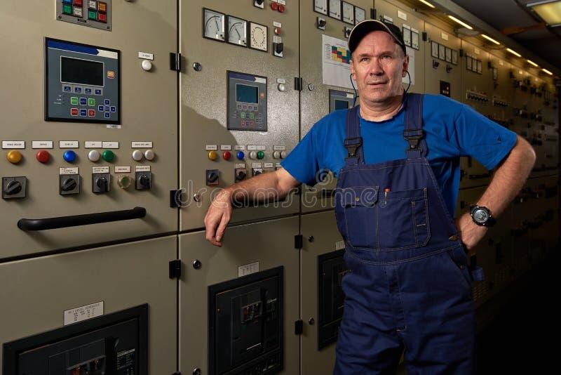 Stolt och lycklig mekaniker/högsta tekniker som poserar med hans armar som korsas i maskinrummet av ett industriellt lastfartyg arkivbild