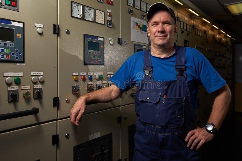 Stolt och lycklig mekaniker/högsta tekniker som poserar med hans armar som korsas i maskinrummet av ett industriellt lastfartyg arkivbilder