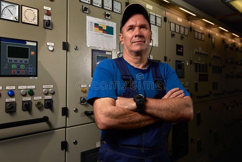 Stolt och lycklig mekaniker/högsta tekniker som poserar med hans armar som korsas i maskinrummet av ett industriellt lastfartyg royaltyfria bilder