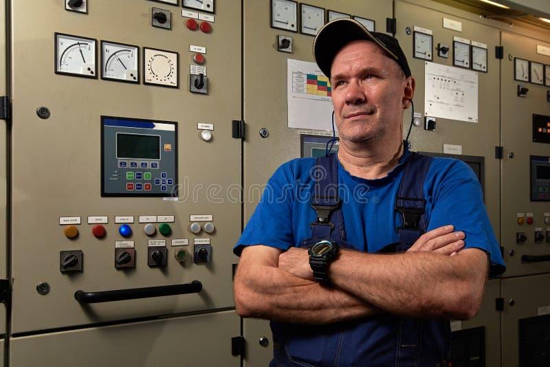 Stolt och lycklig mekaniker/högsta tekniker som poserar med hans armar som korsas i maskinrummet av ett industriellt lastfartyg royaltyfri foto