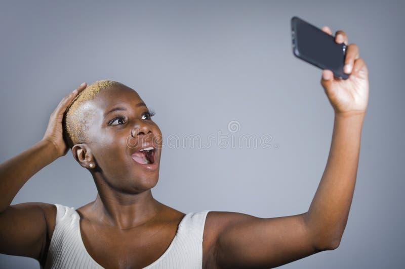 Stolt ung för selfiebild för härlig och lycklig svart afro amerikansk kvinna upphetsad tagande uppvisning hennes rakade head hårs royaltyfri foto