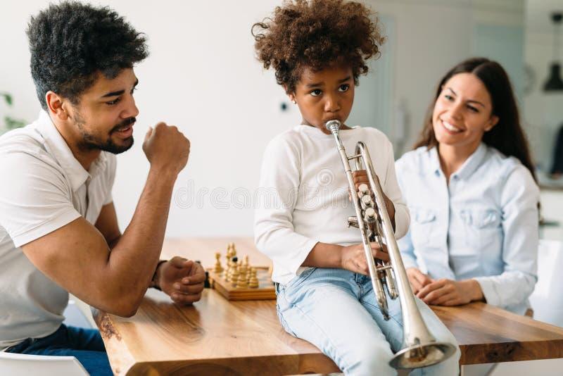 Stolta föräldrar som håller ögonen på deras trumpet för barnlekar royaltyfria bilder