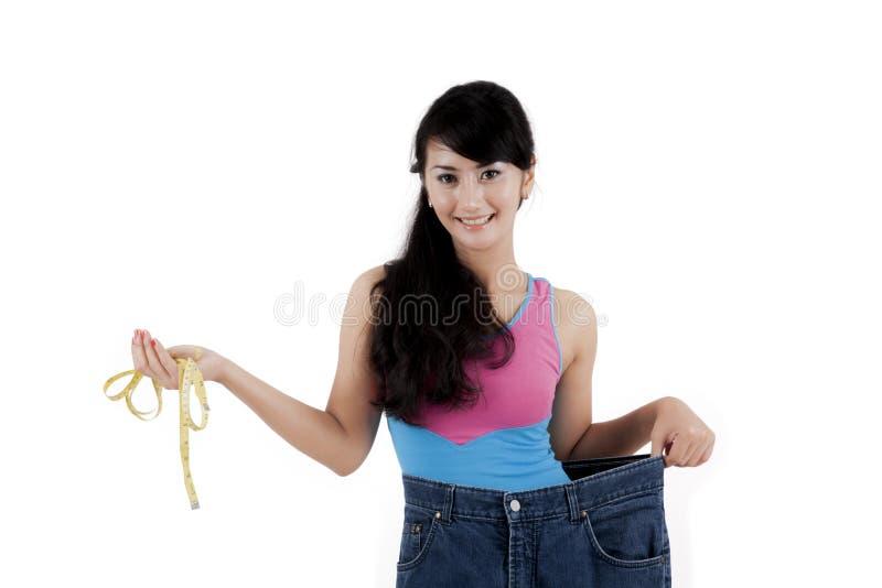 Stolze asiatische Frau, die ihr Gewichtsverlust zeigt lizenzfreie stockfotografie