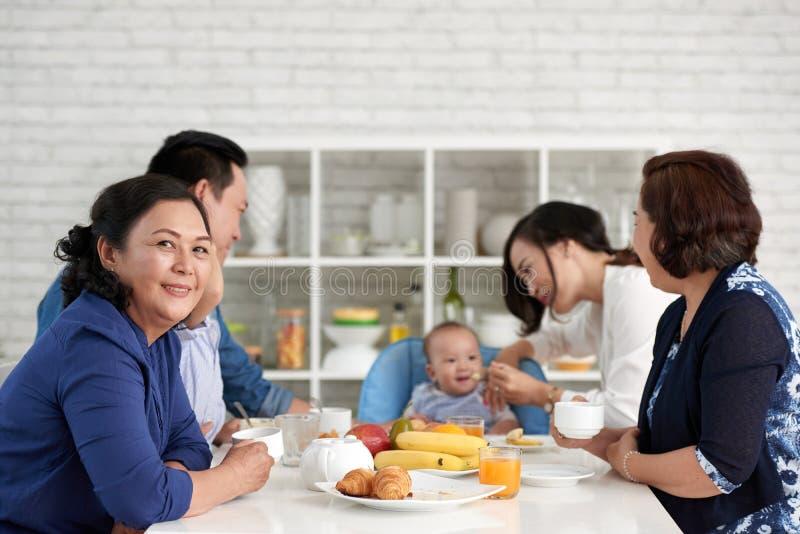 Stolze Großmutter am Frühstück mit Familie lizenzfreie stockfotos