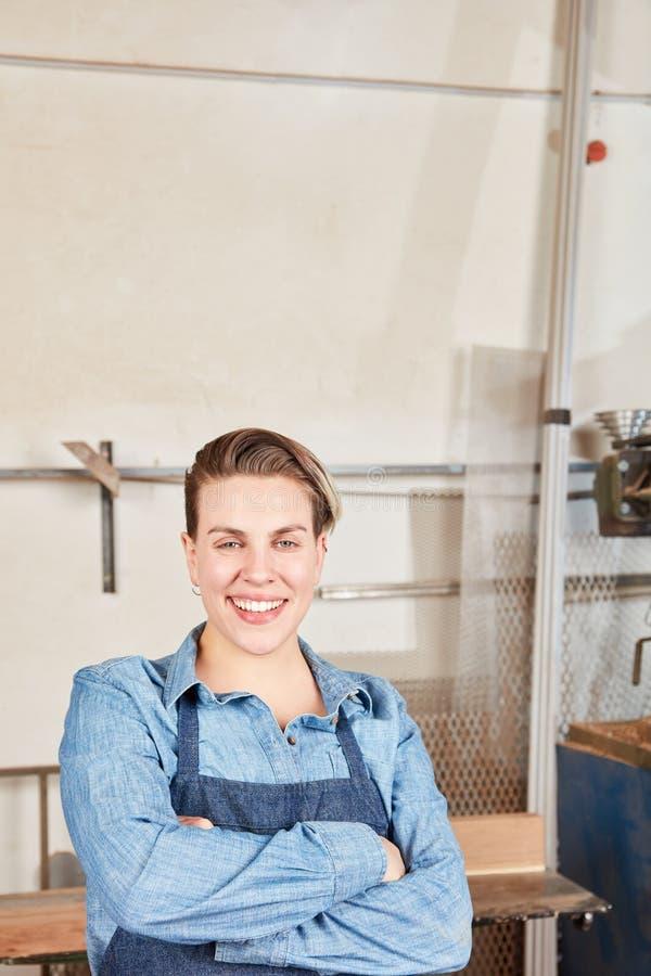Stolze junge Frau als Handwerkerlehrling stockbilder