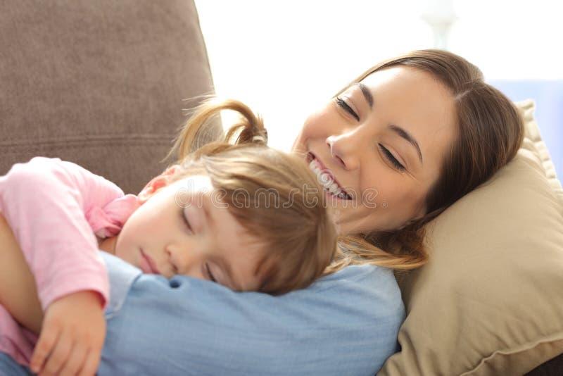 Stolze Mutter, die ihr Babyschlafen aufpasst lizenzfreies stockfoto