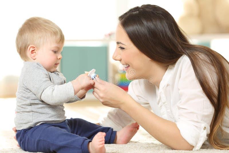 Stolze Mutter, die ihrem Baby einen Friedensstifter gibt stockbilder