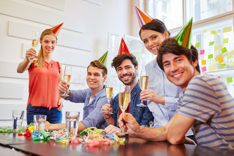 Stolze Studenten, die Erfolg mit Champagner feiern stockfoto