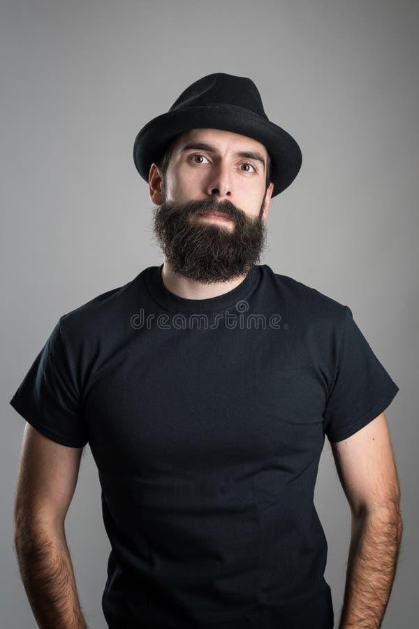 Stolzer überzeugter bärtiger Hippie, der schwarzes T-Shirt und den Hut betrachtet Kamera trägt stockbilder