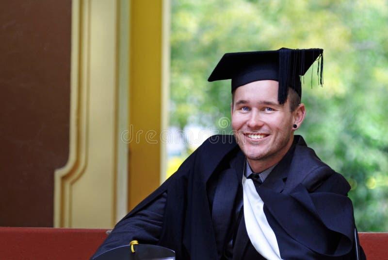 Stolzer Absolvent des jungen Mannes Hochschulnach Graduierungsfeier stockfoto