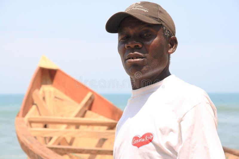Stolzer afrikanischer Fischer mit seinem Boot stockfoto