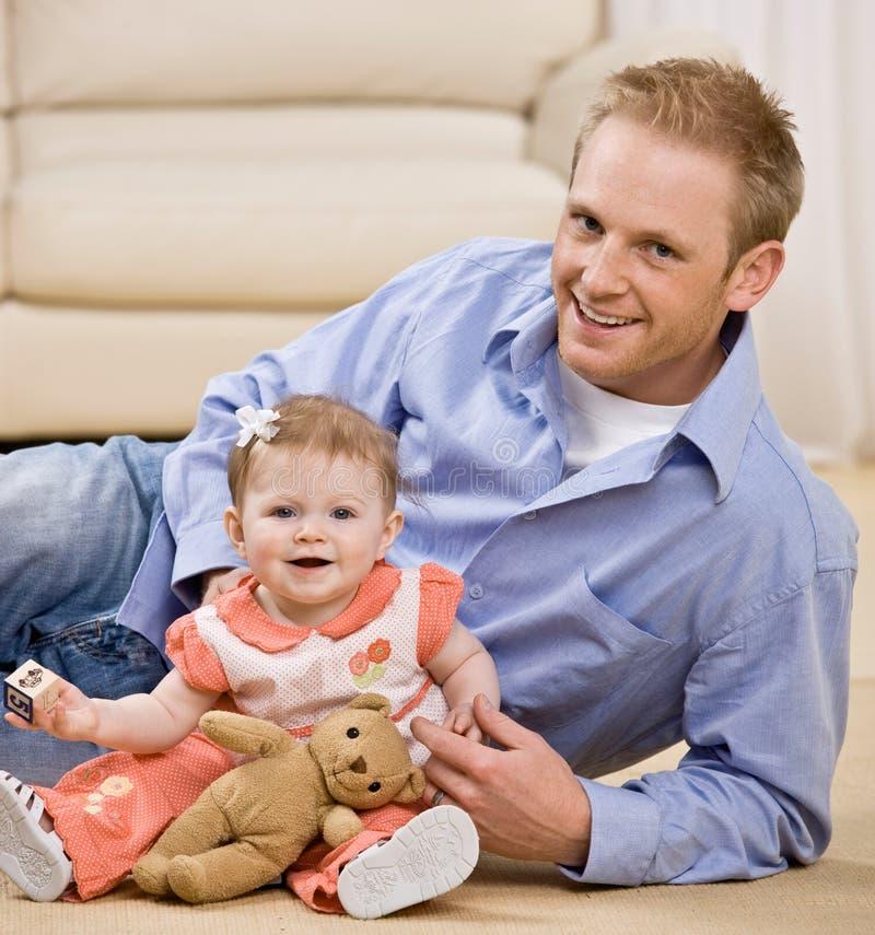 Stolzer junger Vater, der mit Schätzchentochter spielt lizenzfreie stockfotos