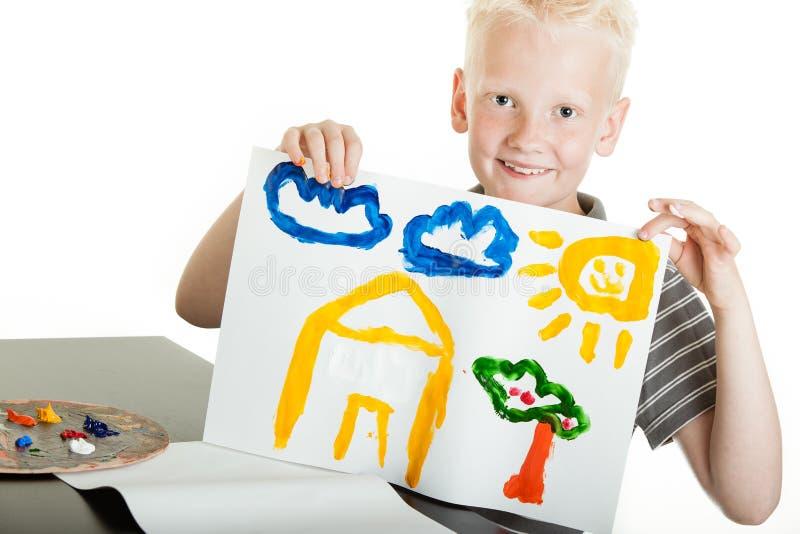 Stolzer kleiner Junge, der eine bunte Malerei hält stockbild