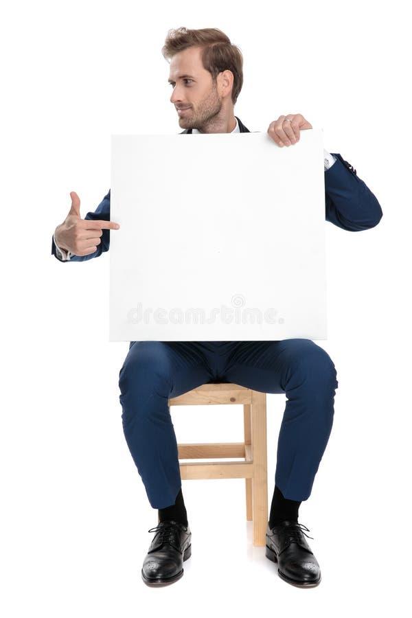 Stolzer Sitzkerl, der seinen Finger auf eine leere Anschlagtafel zeigt stockbild