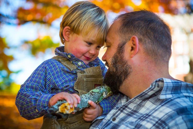 Stolzer Vater, der blonden Jungen im Fall hält stockfotos