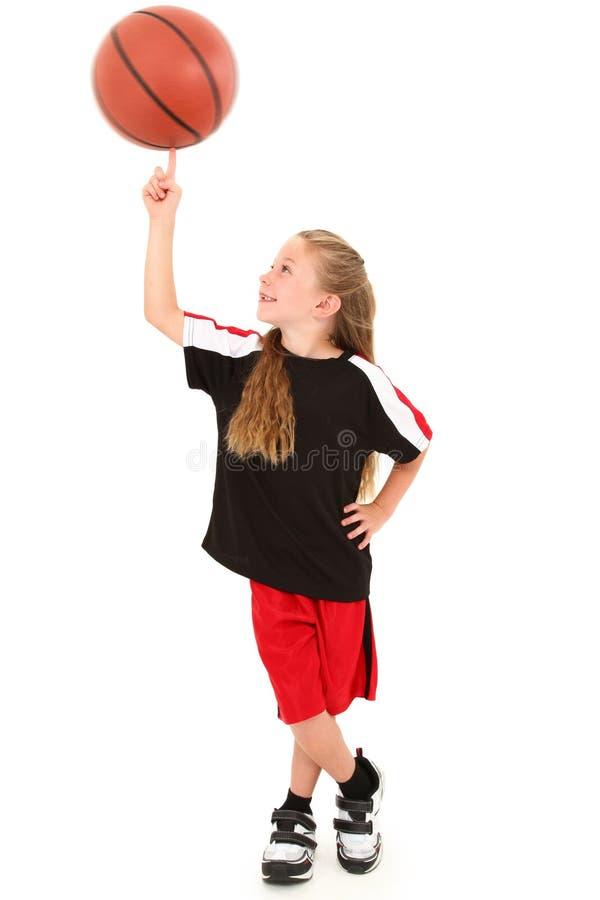 Stolzes Mädchen-Kind-spinnender Basketball auf Finger stockfotos