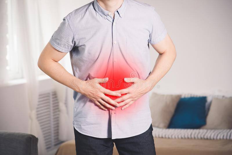 Stomach ache, man with abdominal pain suffering at home. Painful area highlighted in red stock images