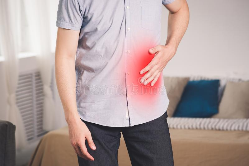 Stomach ache, man with abdominal pain suffering at home. Painful area highlighted in red royalty free stock photos