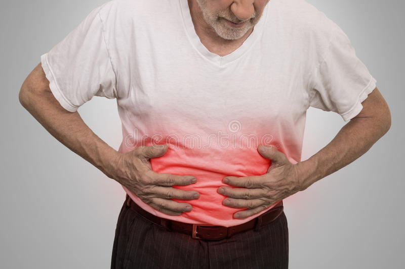 Stomach ache, man placing hands on the abdomen. Isolated on gray wall background stock images