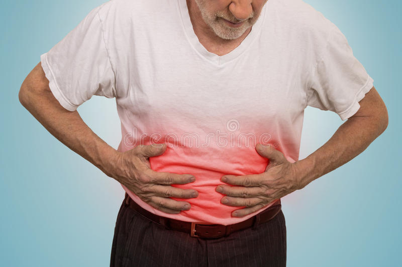 Stomach ache, man placing hands on the abdomen. Isolated on light blue background stock photos