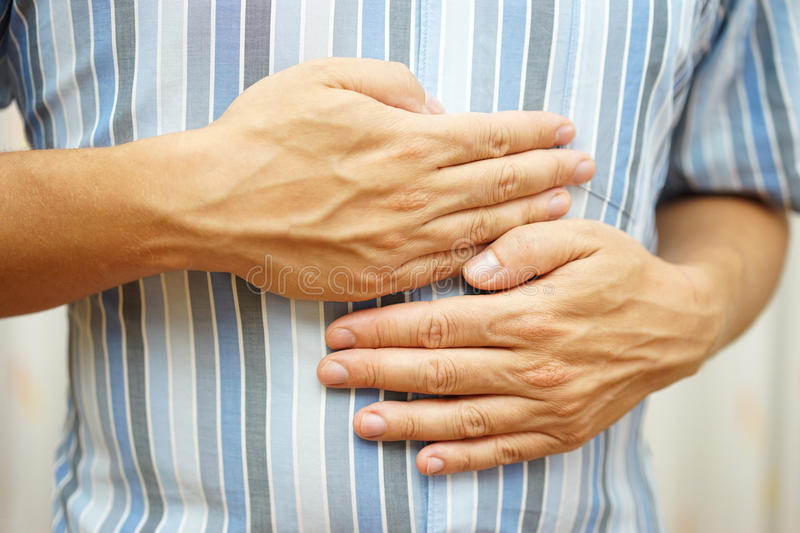 Stomach ache, man placing hands on the stomach, concept of sto. Mach ulcer stock photography