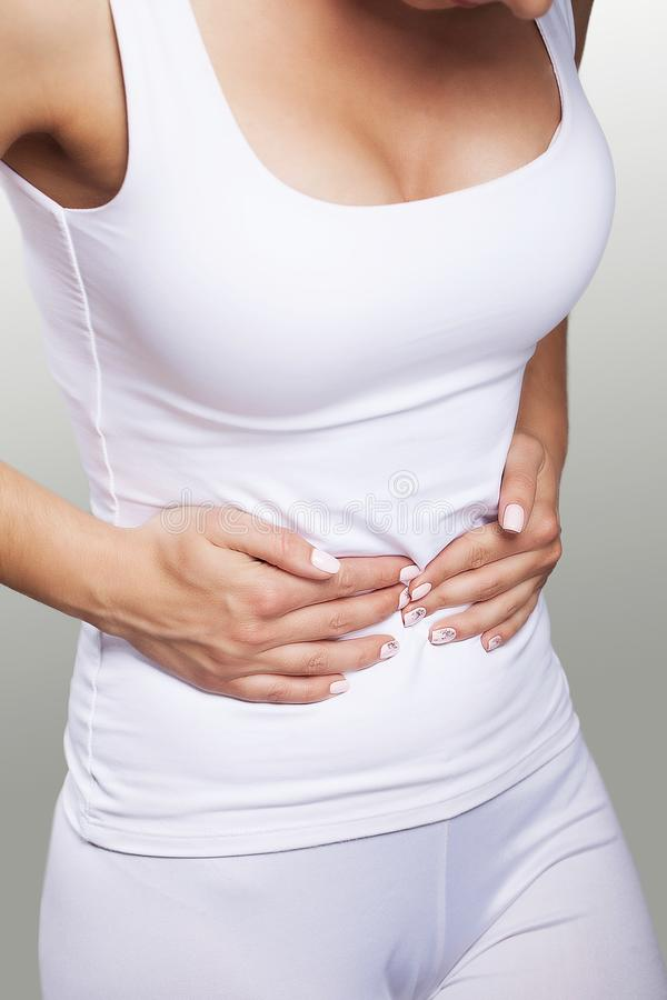 Stomach ache. Painful sensations on the right side of the abdomen. Appendicitis. Young woman holding hands on her stomach. The con stock images