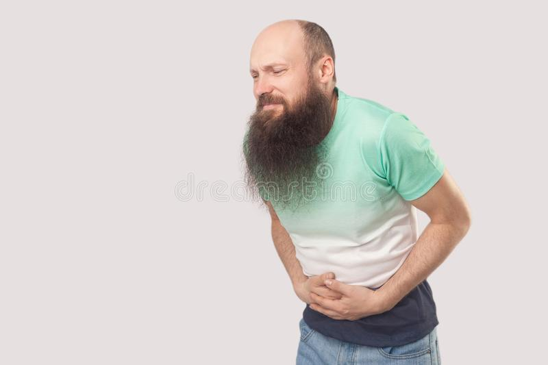 Stomach pain. Portrait of sick middle aged bald man with long beard in light green t-shirt standing, holding his painful belly and royalty free stock image