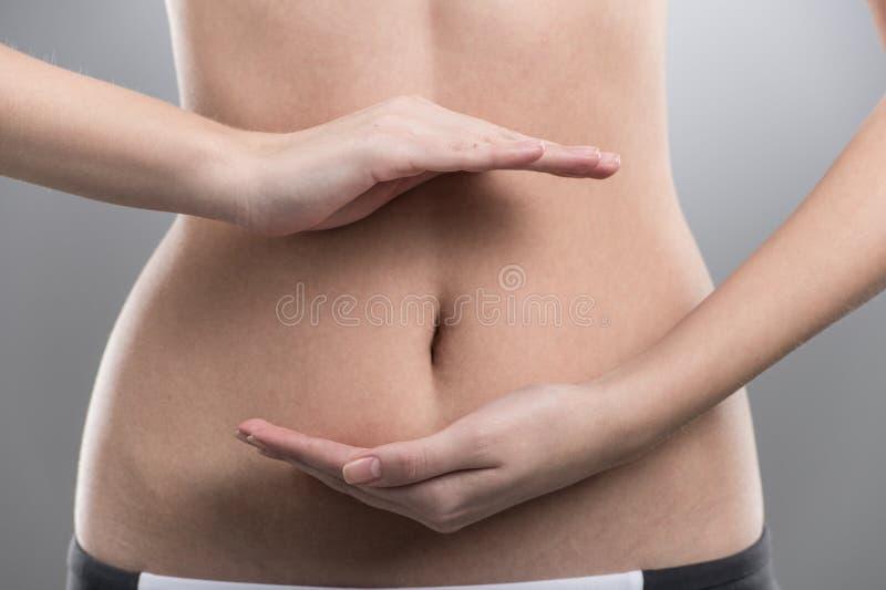Stomaco di forma fisica della ragazza su fondo grigio fotografia stock