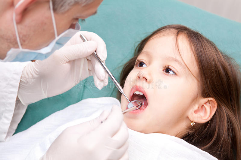 Stomatologic consultation. At the dentist - little girl have a consultation stock images