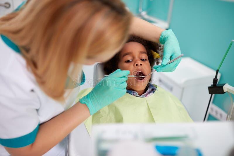 Stomatologicznego asystenta spojrzenie z stomatologicznymi lustrzanymi dziewczyna zębami obraz stock