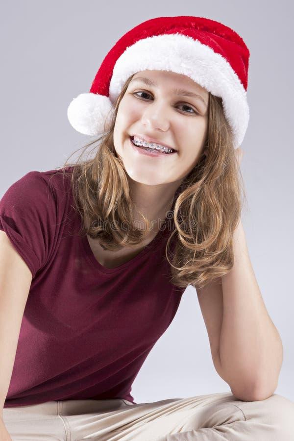 Stomatologiczni pojęcia i pomysły Szczęśliwy Kaukaski nastolatek w Santa kapeluszu Z zębów wspornikami fotografia royalty free