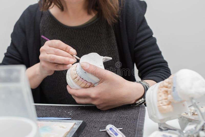 Stomatologiczny technik pracuje na tynku kamienia modelu z cyrkonu mostem i stosować ceramiczny fotografia royalty free